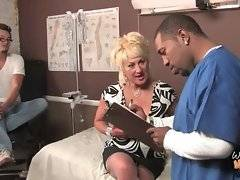 Black doctor examines white milf`s big boobs.