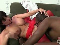 Black fellow takes milf`s high heels off her legs in red stockings and kisses her feet.
