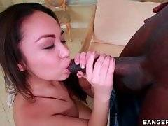Adorable chick kneels down and wraps her lips around huge black cock.